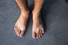 Male feet on a gray summer background. A male feet on a gray summer background Stock Photos