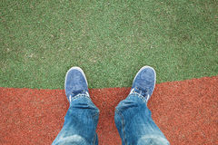 Male feet in jeans and sneakers on a stadium Royalty Free Stock Photography