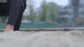 Male feet jumping in the sand outdoors Jumper legs jumping in the sand on the sports field Healthy lifestyle stock footage