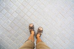 Male feet in leather sandals top view. Male feet in leather sandals first person view Royalty Free Stock Images