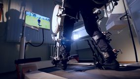 Male feet in low view move and control a VR avatar. Male feet inside an exoskeleton control a human VR avatar on a screen stock video