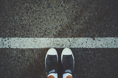 Male feet near white line on asphalt. Male feet in white socks and gumshoes standing near grunge white line on gray asphalted road, ready to go Royalty Free Stock Image