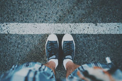 Male feet near white line on asphalt stock photos