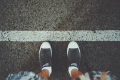 Male feet near white line on asphalt. View of feet of man in white socks and gumshoes standing near grunge white line on gray asphalted road, ready to pass Royalty Free Stock Images