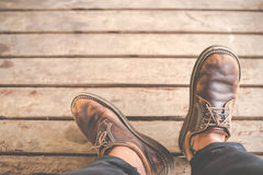 Male feet in old leather shoes Stock Photos