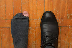Male feet in one Shoe and torn sock Stock Image