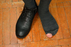 Male feet in one Shoe and torn sock.  royalty free stock photo