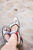 Male feet over the sand. Male wearing sandals feet on the beach Stock Photos