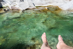Male feet over water of river in sun on vacation Royalty Free Stock Photos
