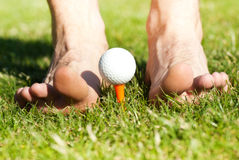Male feet playing with golf ball Stock Photo