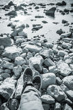 Male feet on rocky coast, blue toned Royalty Free Stock Image