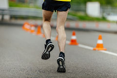 Male feet in running shoes. In road dark asphalt with traffic cones safety Stock Photos