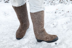 Male feet with Russian felt boots on winter road Royalty Free Stock Images