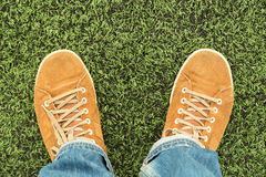 Male feet in shoes on green grass. Man in leather shoes and jeans stands on fresh green grass, top view Royalty Free Stock Images