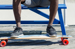 Male feet on skateboard. While sitting on a bench Stock Photos