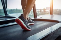 Male feet in sneakers running on the treadmill at the gym. Exercise concept stock photos