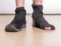 Male feet with sock in hole. One male foot in slippers, other in sock with hole royalty free stock photos