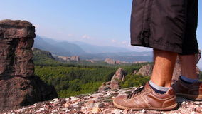 Male feet in sport shoes step on a rock, tourist admire the Belogradchik valley stock video footage