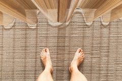 Male feet stand near wide window. Male feet stand in the sunlight near wide window with tulle, top view photo Stock Photography