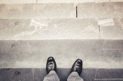 Male feet stand on outdoor stone stairs. Male feet in new black shining leather shoes stand on outdoor stone stairs first person view, vintage tonal correction Stock Photos