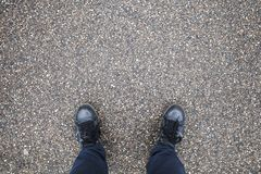 Male feet stand on street asphalt. Male feet in blue jeans and black leather shoes stand on street asphalt pavement Stock Photos