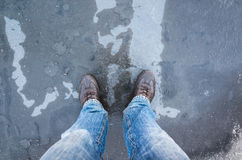Male feet standing on frozen puddle with thin ice Stock Images