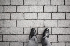 Male feet standing on gray cobblestone road Royalty Free Stock Photo