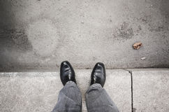 Male feet standing on gray curb Stock Images