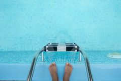 Male feet standing on pier a pool. Royalty Free Stock Photography
