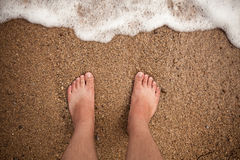Male feet standing on sandy beach Stock Photography