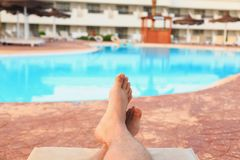 Male feet on swimming pool background stock photo