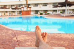 Male feet on swimming pool background stock photography