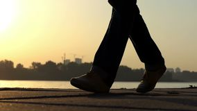 Male feet walk on a river bank at a splendid sunset in slo-mo focusing. An original view of male feet walking on a river bank at a golden sunset in summer in stock video