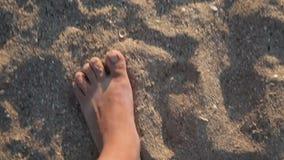 Male feet walking along sandy beach stock video footage