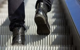 Male feet walking in boots up escalator Stock Image