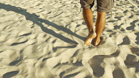 Male feet walking on sand. Tanned man crossing desert barefoot. Human footsteps on beach. Survival on uninhabited island concept. Back view Stock Photos