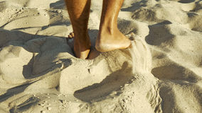 Male feet walking on sand. Tanned man crossing desert barefoot. Human footsteps on beach. Survival on uninhabited island concept. Back view Royalty Free Stock Image