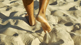 Male feet walking on sand. Tanned man crossing desert barefoot. Human footsteps on beach. Survival on uninhabited island concept. Back view Royalty Free Stock Photos