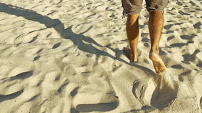 Male feet walking on sand. Tanned man crossing desert barefoot. Human footsteps on beach. Survival on uninhabited island concept. Back view Royalty Free Stock Images