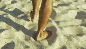 Male feet walking on sand. Tanned man in khaki shorts crossing desert barefoot. Human footsteps on beach. Survival on uninhabited island concept. Close-up