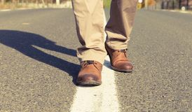 Male feet walking and wearing atutumn leather shoes. Male feet walking and wearing atutumn real leather shoes. Center of the asphalt road Stock Photos