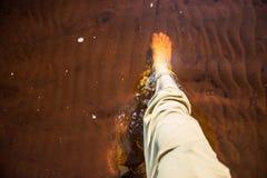 Male feet in water. Male legs splashing sea water Royalty Free Stock Image