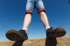Male feet wearing sneakers outdoor. Male feet wearing black sneakers outdoor wide angle view Stock Photography