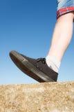Male feet wearing sneakers outdoor. Male feet wearing black sneakers outdoor wide angle view Royalty Free Stock Image