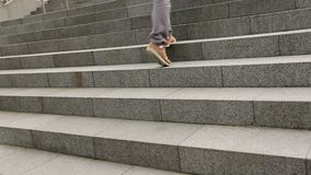 Male feet wearing sneakers running up the stairs, student walking to university. Stock footage stock footage