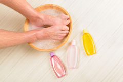 Male feets in a bowl. Male feet in a bowl with water and soap, cosmetics in bottles, hygiene and spa concept Royalty Free Stock Photo