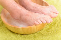 Male feets in a bowl. Male feet in a bowl with water and soap, hygiene and spa concept Royalty Free Stock Images