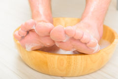 Male feets in a bowl. Male feet in a bowl with water and soap, hygiene and spa concept Royalty Free Stock Photography