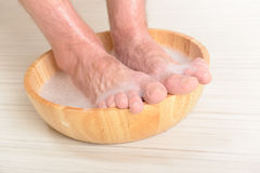 Male feets in a bowl. Male feet in a bowl with water and soap, hygiene and spa concept Stock Photos