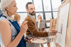 Male and female adult students painting together. At art class Stock Photos
